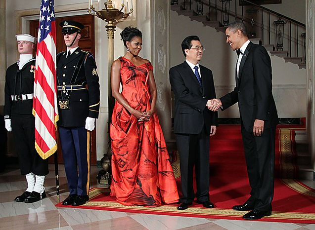 President Barack Obama and first lady Michelle Obama greet China's President Hu Jintao at the Grand Staircase as they arrive for a state dinner at the White House in Washington, Wednesday, Jan. 19, 2011. (AP Photo/Carolyn Kaster)