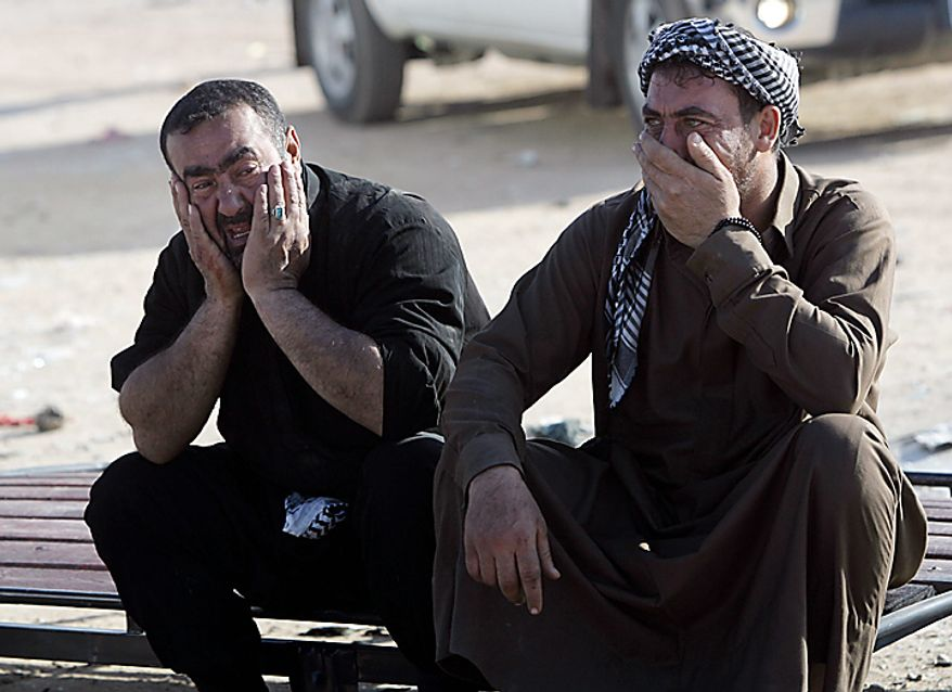 Men grieve after a bombing in Karbala, 50 miles south of Baghdad, Iraq, Thursday, Jan. 20, 2011. A pair of bombs blasted through security checkpoints ringing the Iraqi holy city of Karbala Thursday and killed scores, most of whom were Shi'ite pilgrims headed to observe yearly religious rituals. (AP Photo/Ahmed al-Husseini)