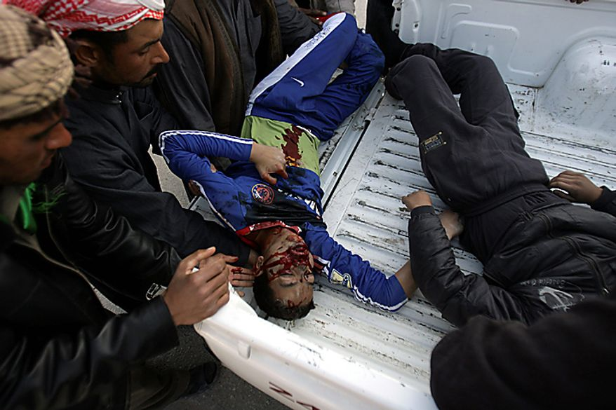 The body of a man killed in a bombing is loaded on the back of a truck in Karbala, 50 miles south of Baghdad, Iraq, Thursday, Jan. 20, 2011. A pair of bombs blasted through security checkpoints ringing the Iraqi holy city of Karbala Thursday and killed scores of people, many of whom were Shi'ite pilgrims headed to observe yearly religious rituals. (AP Photo/Ahmed al-Husseini)