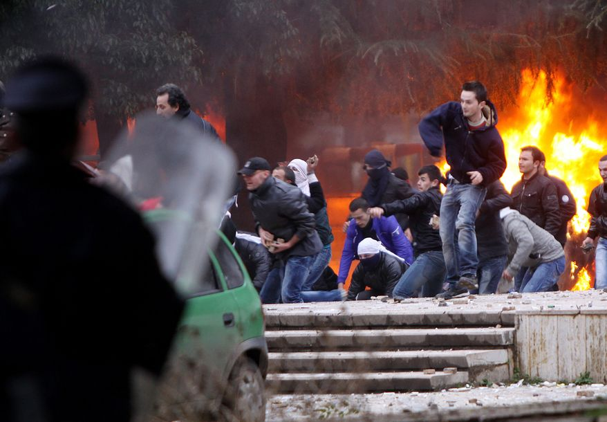 Opposition protesters throw stones at police after a pro-opposition rally Friday, Jan. 21, 2011. At least three people were reported dead as more than 20,000 people attended a rally organized by the socialist party to demand that that conservative Prime Minister Sali Berisha call early elections because of a corruption scandal.(AP Photo/Visar Kryeziu)
