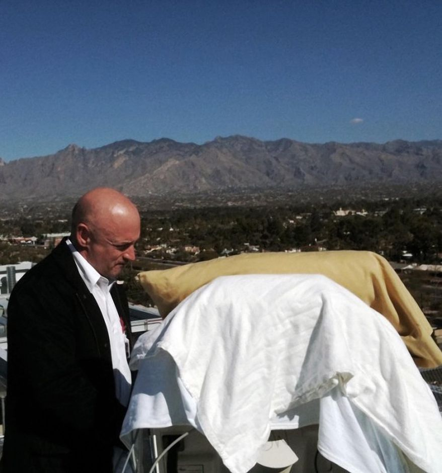 In this photo provided by the office of U.S. Rep Gabrielle Giffords, Mrs. Giffords' husband, Mark Kelly, stands with his wife as she looks from her bed at the Santa Catalina Mountains while on an outdoor deck at University Medical Center in Tucson, Ariz., Thursday, Jan. 20, 2011. Mrs. Giffords is scheduled to be flown to Houston on Friday to begin her rehabilitation. (AP Photo/Office of U.S. Rep. Gabrielle Giffords)
