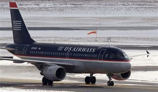 ** FILE ** In this Thursday, Jan. 20, 2011, photo a U.S. Airways jet taxies on the tarmac at Boston's Logan International Airport. (AP Photo/Stephan Savoia)