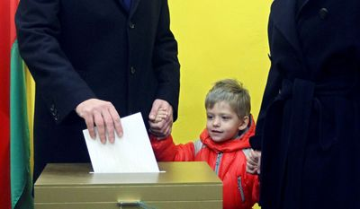 Opposition presidential candidate Andrei Sannikov casts his ballot as his wife, Irina Khalip, and son, Danil, look on at a polling station in Minsk last month. (Associated Press)