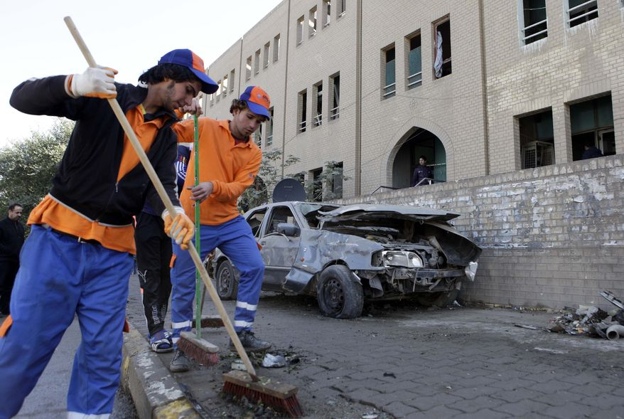 Workers sweep away debris after a bombing in Baghdad on Sunday, Jan. 23, 2011. A flurry of morning blasts killed and wounded several across the city, police said, in what one Iraqi official called an attempt to undermine security ahead of a much anticipated meeting of Arab heads of state in two months. (AP Photo/Karim Kadim)