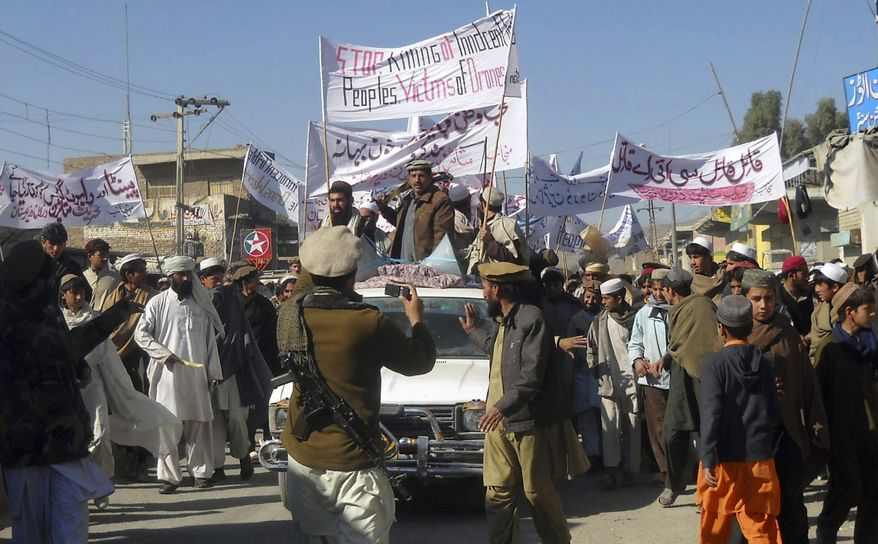 """Pakistani tribesmen protest in Mir Ali, Pakistan, on Sunday, Jan. 23, 2011, to demand an end to U.S. drone strikes. The banner reads: """"Stop killing of innocent peoples. Victims of Drones."""" A pair of suspected strikes killed six militants in Pakistan's troubled North Waziristan tribal area near the Afghan border on Sunday, Pakistani intelligence officials said. (AP Photo/Rasool Dawar)"""