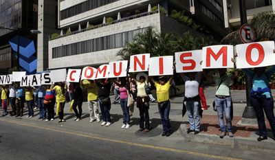 "People hold up signs with letters forming a phrase that reads ""No more communism"" in Spanish during a demonstration Sunday in Caracas, Venezuela, marking a new anniversary of the overthrow of Venezuela's last dictator Gen. Marcos Perez Jimenez. Opposition supporters gathered along an avenue in eastern Caracas and chanted anti-government slogans while waving Venezuelan flags. (Associated Press)"