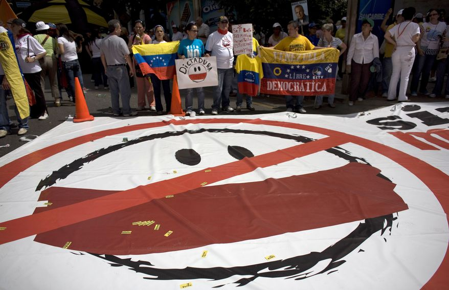 People holds up Venezuelan flags during a demonstration Sunday in Caracas, Venezuela, marking a new anniversary of the overthrow of Venezuela's last dictator Gen. Marcos Perez Jimenez. Opposition supporters gathered along an avenue in eastern Caracas and chanted anti-government slogans while waving Venezuelan flags. (Associated Press)