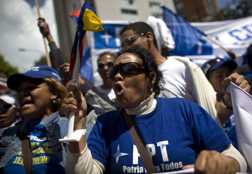 People chant anti-government slogans during a demonstration Sunday in Caracas, Venezuela, marking a new anniversary of the overthrow of Venezuela's last dictator Gen. Marcos Perez Jimenez. Opposition supporters gathered along an avenue in eastern Caracas and chanted anti-government slogans while waving Venezuelan flags. (Associated Press)