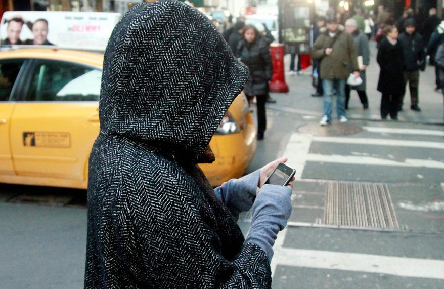 A pedestrian uses a phone in a crosswalk in New York. While electronic devices changed popular culture by offering an ability to always stay connected, it turned into such a need that a simple walk is considered wasted time. (Associated Press)