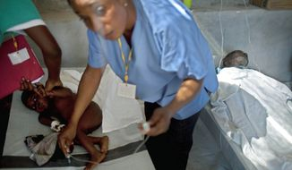 Nurses examine a child suffering cholera symptoms at a Doctors Without Borders cholera clinic in Saint-Marc on Saturday. A new network of cholera-treatment centers staffed by Haitian doctors and nurses, nongovernmental organizations and international volunteers has made it easier for victims to get oral and intravenous rehydration. The disease is relatively easy to treat if caught in time. (Associated Press)