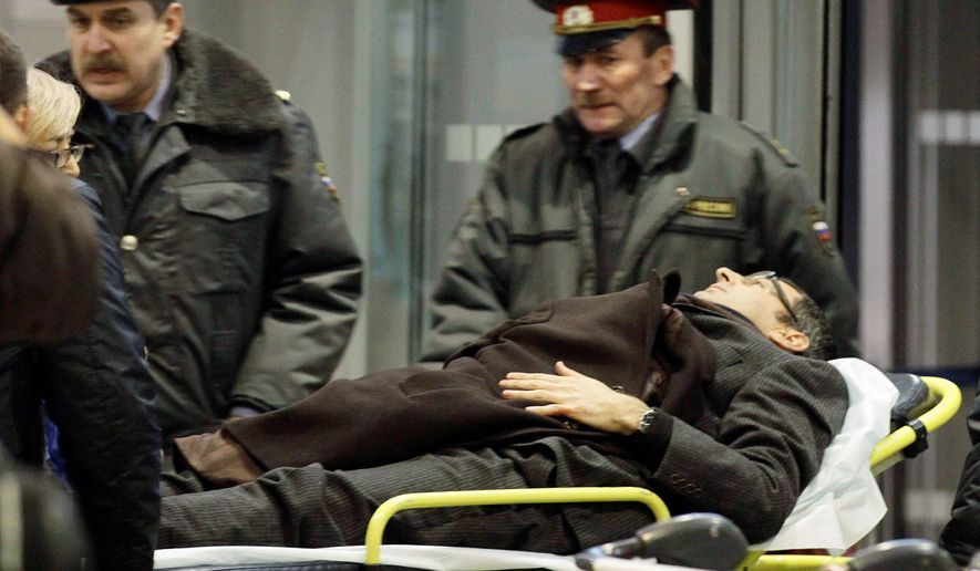 CARNAGE: A man injured in an explosion is evacuated Monday from Moscow's Domodedovo Airport. Analysts suspect the suicide bombing was linked to the Caucasus Emirate. (Associated Press)