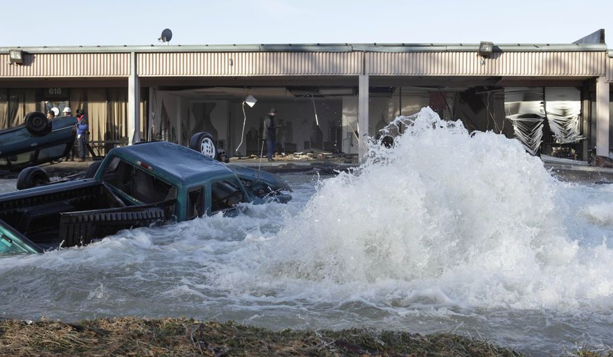 A water-main break at an industrial park next to the Capital Beltway in Capitol Heights, Md., on Monday, Jan. 24, 2011, sent water pouring from a 54-inch pipe and onto the highway, prompting the closure of the Inner Loop during the morning rush hour. (AP Photo/Jacquelyn Martin)