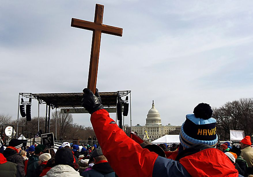 A man holds a cross during an anti-abortion rally on the National Mall in Washington on Monday, Jan. 24, 2011. The anniversary of the Supreme Court's Roe v. Wade decision was Saturday. (AP Photo/Alex Brandon)