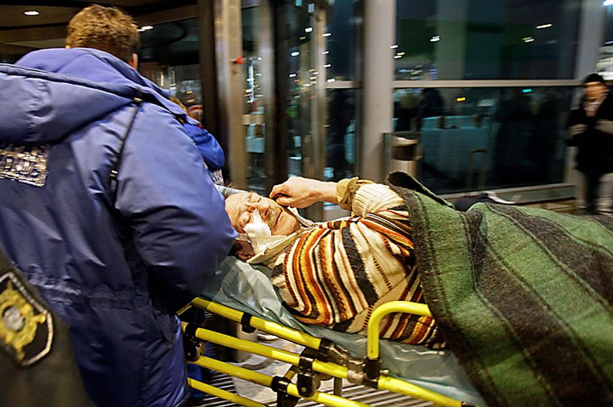 ** FILE ** A man wounded in a blast is carried away at Domodedovo Airport in Moscow on Monday, Jan. 24, 2011. An explosion ripped through the international arrivals hall at the city's busiest airport, killing dozens of people and wounding scores, officials said. Russian President Dmitry Medvedev called it a terror attack. (AP Photo/Ivan Sekretarev)