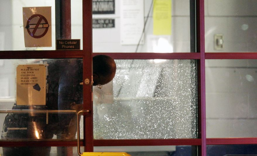 A Detroit police officer looks over one of the plate glass windows that was hit inside the precinct building in northwest Detroit where a gunman walked into the police station and opened fire injuring four police officers on Sunday. The gunman was killed. (Associated Press)