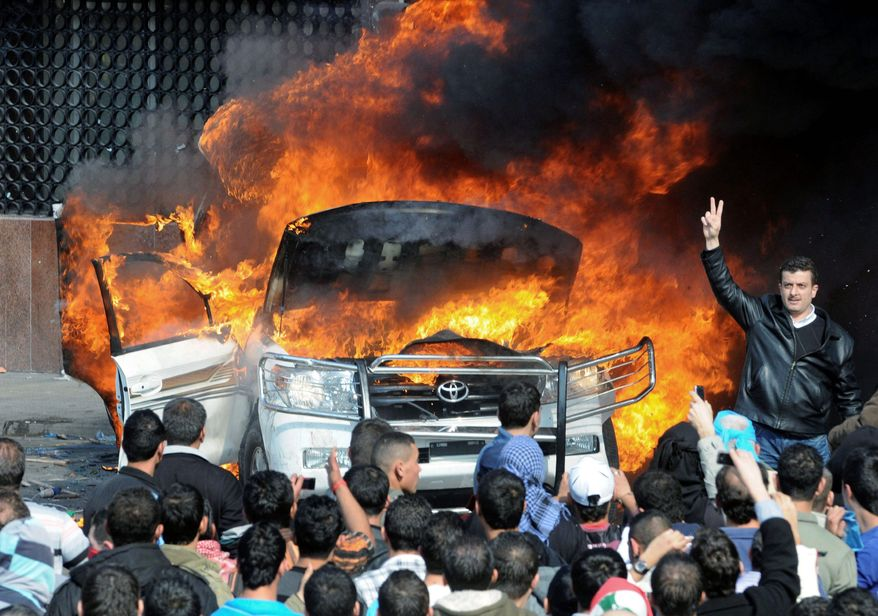 Protesters burn a van belonging to Al Jazeera news network in Tripoli, Lebanon, in one of the demonstrations Tuesday against the appointment of Najib Mikati as prime minister. Sunni protesters accused Al Jazeera of backing Shiite Hezbollah, which put forth Mr. Mikati for the post. (Associated Press)