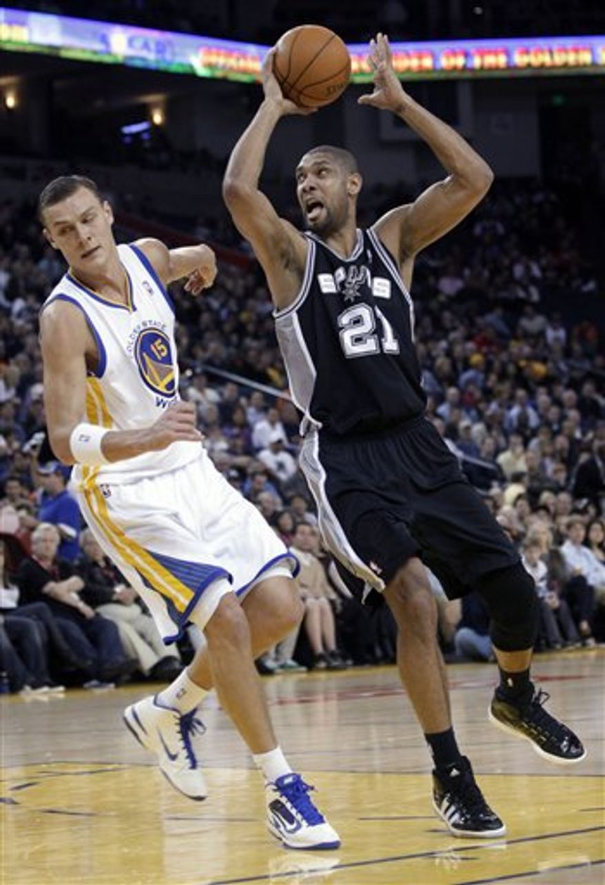 San Antonio Spurs center Tim Duncan (21) works against Golden State Warriors' Andris Biedrins, of Latvia, during the first half of an NBA basketball game in Oakland, Calif., Monday, Jan. 24, 2011. (AP Photo/Marcio Jose Sanchez)