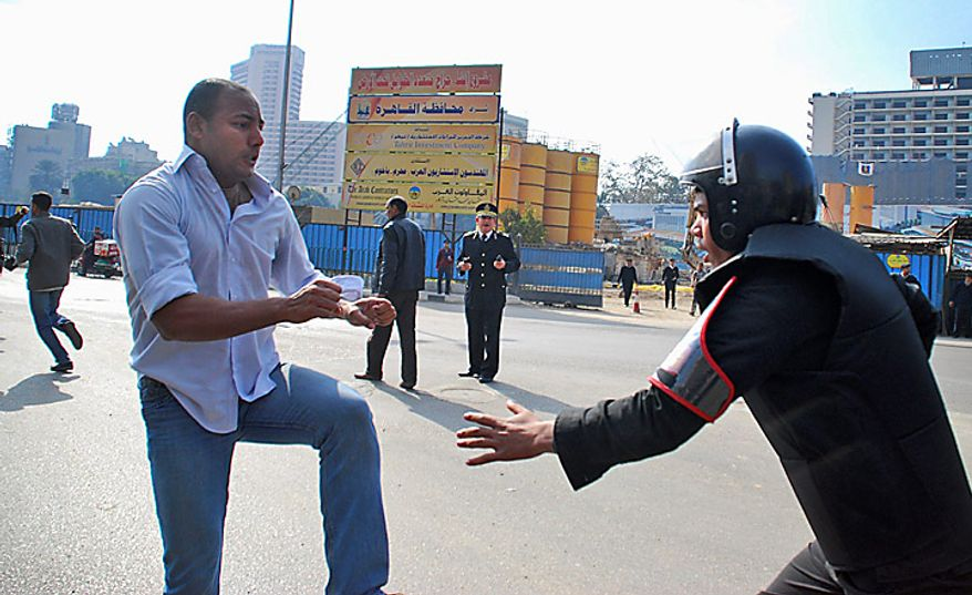 A protester confronts a riot policeman as he demonstrates in downtown Cairo, Egypt, Tuesday, Jan. 25, 2011. Hundreds of anti-government protesters marched in the Egyptian capital chanting against President Hosni Mubarak and calling for an end to poverty. (AP Photo/Mohammed Abu Zaid)