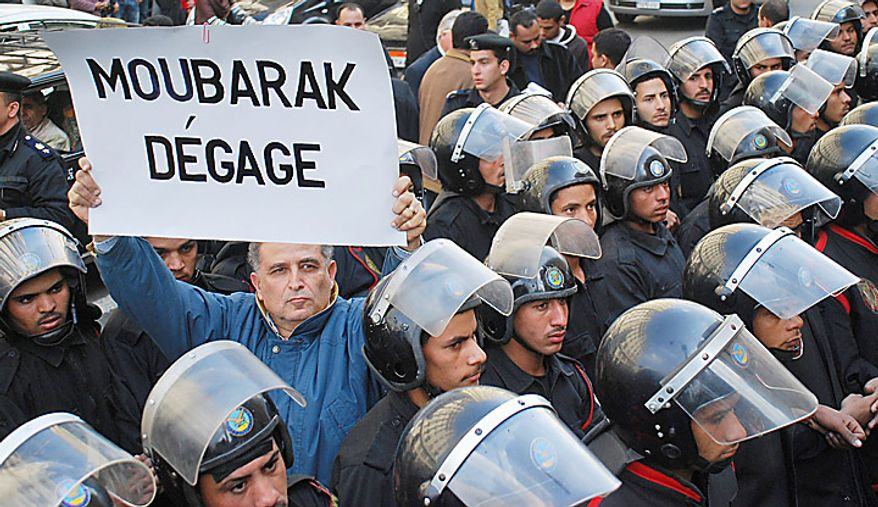 """A protester holding a placard in French reading """"Mubarak, get out"""" is surrounded by riot police during a demonstration in downtown Cairo, Egypt, Tuesday, Jan. 25, 2011. Anti-government protesters marched in the Egyptian capital chanting against President Hosni Mubarak and calling for an end to poverty. (AP Photo/Mohammed Abu Zaid)"""
