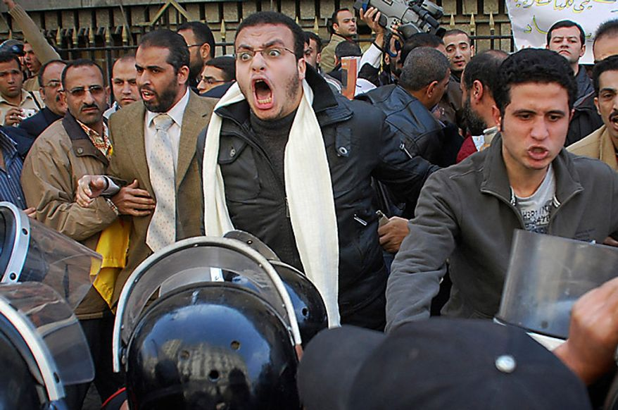Protesters are confronted by riot police as they demonstrate in downtown Cairo, Egypt, Tuesday, Jan. 25, 2011. Hundreds of anti-government protesters marched in the Egyptian capital chanting against President Hosni Mubarak and calling for an end to poverty. (AP Photo/Mohammed Abu Zaid)