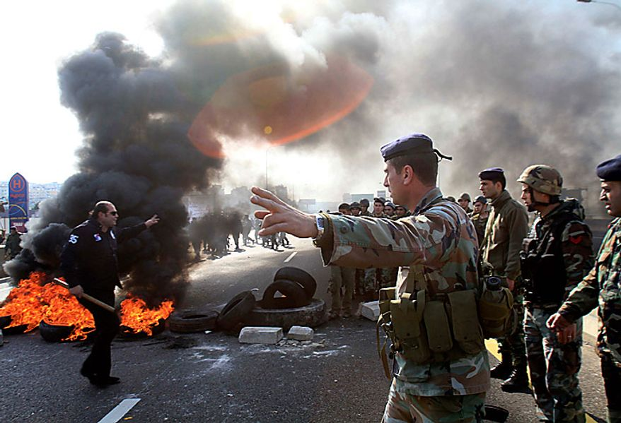 "Lebanese soldiers arrive to open the road after protesters burned tires on the highway in Jiyeh, south of Beirut, Tuesday, Jan. 25, 2011. Thousands of Sunnis waved flags and burned tires Tuesday in a ""day of rage"" to protest gains by the Shi'ite militant group Hezbollah, which is on the brink of controlling Lebanon's next government. (AP Photo/Mohammed Zaatari)"
