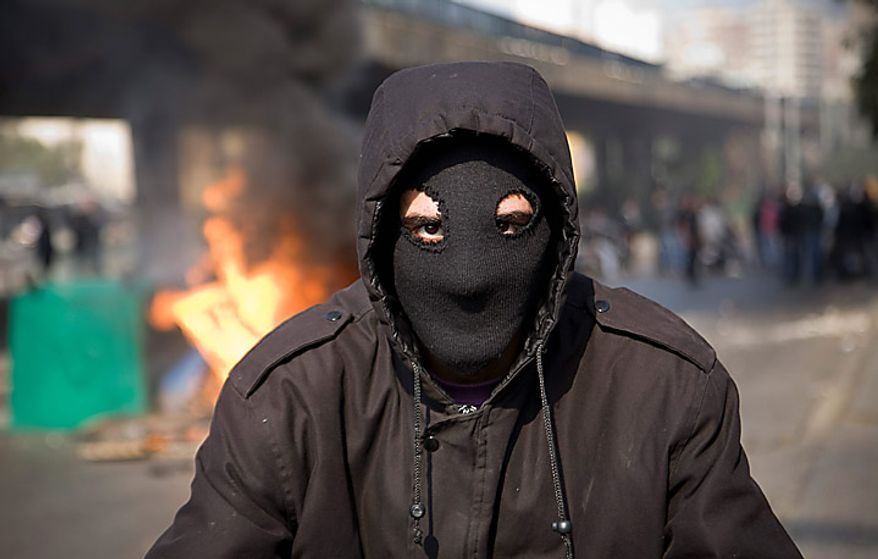 "A masked protester poses in front of burning garbage containers in Beirut, Lebanon, Tuesday, Jan. 25, 2011. Thousands of Sunnis waved flags and burned tires Tuesday in a ""day of rage"" to protest gains by the Shi'ite militant group Hezbollah, which is on the brink of controlling Lebanon's next government. (AP Photo/Grace Kassab)"