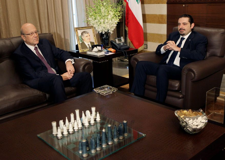Lebanon's caretaker Prime Minister Saad Hariri (right) meets with Prime Minister-designate Najib Mikati at Mr. Hariri's residence in Beirut on Wednesday. Lebanon's new Hezbollah-backed prime minister began the process of forming a new Cabinet on Wednesday, as calm returned to the country after two days of protests against the Iranian-backed militant group's growing influence. (Associated Press)
