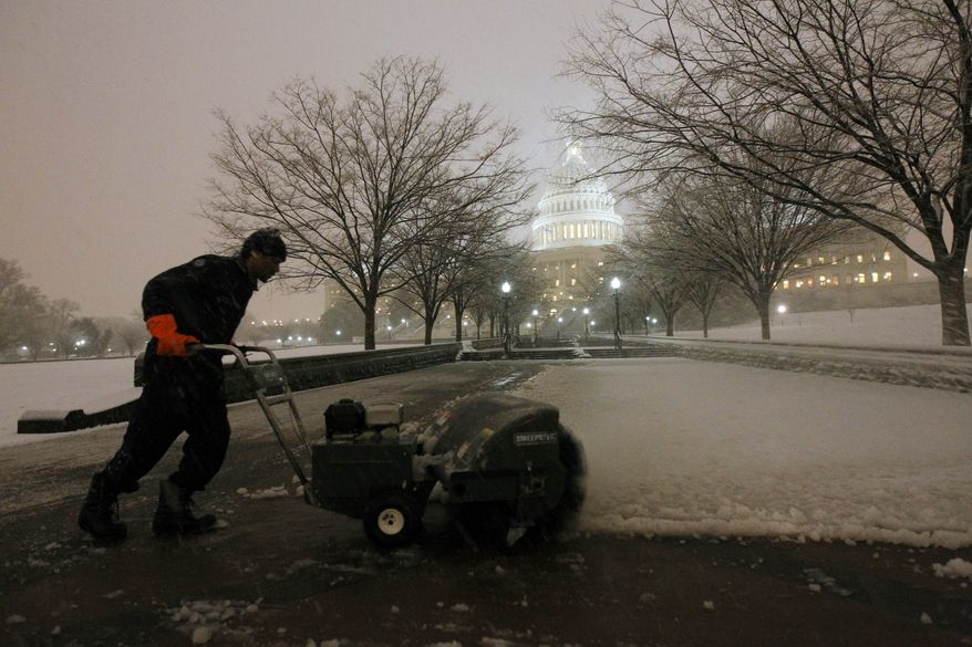 Deonte Lane works to remove the snow on the grounds of the U.S. Capitol as the snow continues to fall on Capitol Hill in Washington, Wednesday, Jan. 26, 2011.(AP Photo/Alex Brandon)
