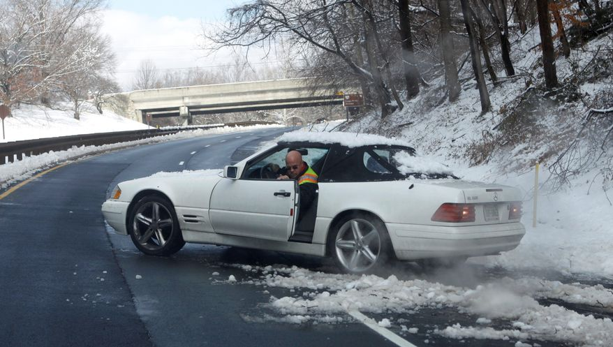 A tow truck operator attempts Thursday to free a car that had been stuck in the snow along the northbound George Washington Parkway in McLean, Va. More snow is predicted for Friday, though the National Weather Service said the Washington area should expect only about an inch. (Associated Press)
