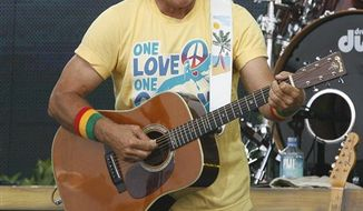 FILE - In this July 11, 2010 file photo, Jimmy Buffett performs in Gulf Shores, Ala. Buffett fell off a stage at the end of a concert in Sydney, Wednesday, Jan. 26, 2011, and was rushed to the hospital. Australia's Daily Telegraph reports that audience members saw the 64-year-old fall face first off the stage and hit his head. (AP Photo/Chip English, file)