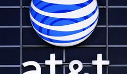 ** FILE ** The AT&T logo is displayed on the side of a corporate office in Springfield, Ill., in July 2010. (AP Photo/Seth Perlman, File)