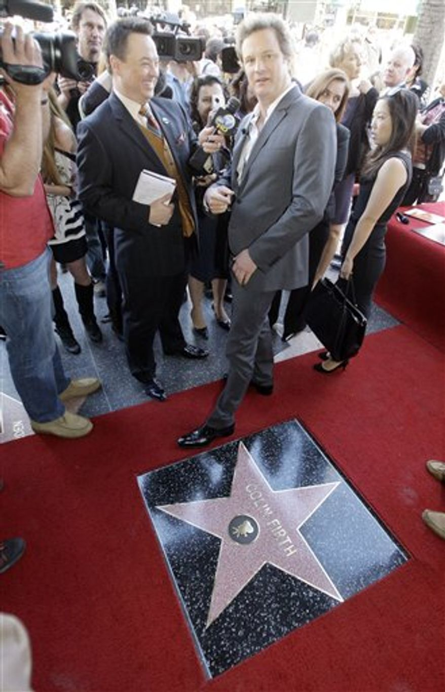 """FILE - In this Jan. 13, 2011 file photo, British actor Colin Firth, star of """"The King's Speech,"""" points back to the Pig 'N' Whistle Pub as he is interviewed during dedication ceremonies for his new star on the Hollywood Walk of Fame in Los Angeles. Every year around now, tens of thousands of DVDs of movies still shown in theaters are sent by movie studios to Oscar, Golden Globe and other awards voters. Every year, some of these discs are copied, and the movies end up being shared online, where they can cut into movie-ticket and DVD sales.(AP Photo/Reed Saxon, file)"""