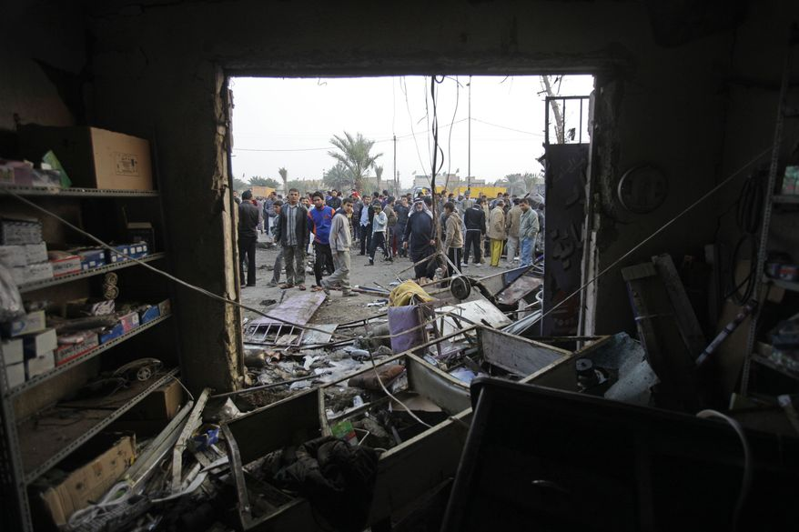 People gather around a destroyed shop at the scene of a car bomb attack in Baghdad, Iraq, on Thursday, Jan. 27, 2011. A car bomb ripped through a funeral tent in a mainly Shiite area of Baghdad on Thursday, killing and wounding scores of people and prompting scuffles between police and Iraqis angry about security failures. (AP Photo/Khalid Mohammed)