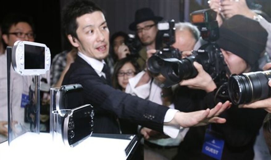 """Sony Computer Entertainment President and CEO Kazuo Hirai shows a new PlayStation Portable """"NGP"""" at PlayStation Meeting 2011 in Tokyo Thursday, Jan. 27, 2011. Sony says the upgraded version of its PlayStation Portable machine will go on sale late this year. (AP Photo/Shizuo Kambayashi)"""