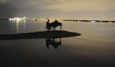 In this Jan. 2, 2011, photo provided by Nicholas Harrington, Julian Kolevris-Roots, 18, is shown sitting at a piano on a sandbar in Miami's Biscayne Bay. Nicholas, a 16-year-old looking to boost his college application, says he is responsible for putting a grand piano on a Biscayne Bay sandbar. (AP Photo/Nicholas Harrington)