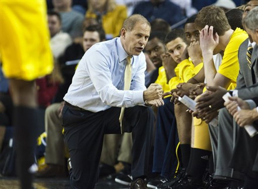 FILE - In this Dec. 28, 2010, file photo, Michigan head coach John Beilein kneels to speak with his bench players during a free throw break in the second half of an NCAA college basketball game against Purdue at Crisler Arena in Ann Arbor, Mich. Young players are supposed to have trouble picking up coach Beilein's complex offense, but it's Michigan's defense that's given the Wolverines problems lately. (AP Photo/Tony Ding, File)