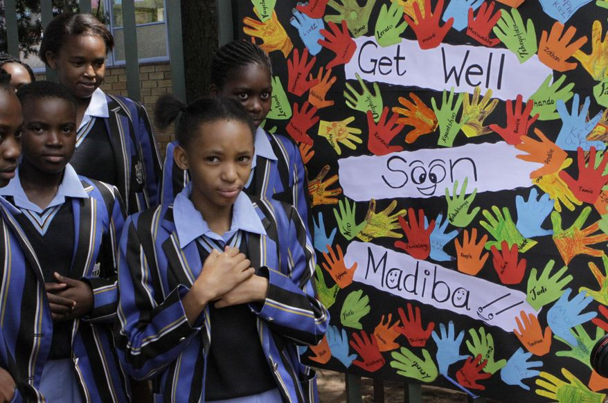 """Students from a school adjacent to the hospital where former South African President Nelson Mandela, fondly known as """"Madiba"""", is said to be undergoing routine tests make their way past a giant get well card Thursday, Jan. 27, 2011. (AP Photo/Denis Farrell)"""