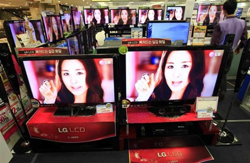 Shoppers walk by a logo of LG Electronics at a local electronic department store in Seoul, South Korea, Wednesday, Jan. 26, 2011. LG Electronics has reported its first quarterly loss in nearly two years amid continued weakness in its mobile phone business. LG Electronics said Wednesday that it lost 256.4 billion won ($229.4 million) in the three months that ended Dec. 31. (AP Photo/Lee Jin-man)