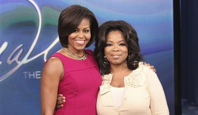 """In this photo taken Jan. 21, 2011 and provided by Harpo Productions Inc., talk-show host Oprah Winfrey, right, poses with first lady Michelle Obama during taping of """"The Oprah Winfrey Show"""" at Harpo Studios in Chicago. The show will air nationally on Thursday, Jan. 27. (AP Photo/Harpo Productions Inc., George Burns)  NO SALES"""