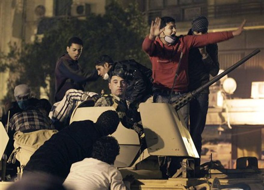 An Egyptian Army soldier riding in an armored personnel carrier is surrounded by anti-government protesters near Tahrir square in Cairo, Egypt, Friday, Jan. 28, 2011. (AP Photo/Ben Curtis)