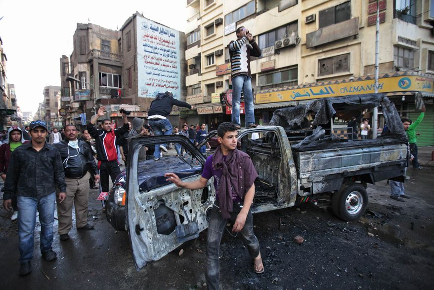 Egyptian anti-government activists, some standing on a burned police car challenge riot police officers, not seen, during clashes in Cairo, Egypt, on Friday Jan. 28, 2011. (AP Photo/Lefteris Pitarakis)