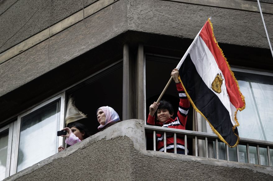 A youth waves an Egyptian flag as people watch from a balcony during a demonstration by anti-government activists, in Cairo Friday, Jan. 28, 2011. Tens of thousands of anti-government protesters poured into the streets of Egypt Friday, stoning and confronting police who fired back with rubber bullets and tear gas in the most violent and chaotic scenes yet in the challenge to President Hosni Mubarak's 30-year rule. (AP Photo/Ben Curtis)