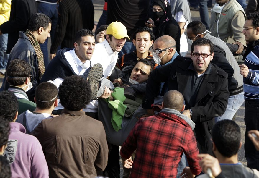 Egyptian anti-government activists carry a wounded man during clashes with the police in Cairo Friday, Jan. 28, 2011. Tens of thousands of anti-government protesters poured into the streets of Egypt Friday, stoning and confronting police who fired back with rubber bullets and tear gas in the most violent and chaotic scenes yet in the challenge to President Hosni Mubarak's 30-year rule. (AP Photo/Ben Curtis)