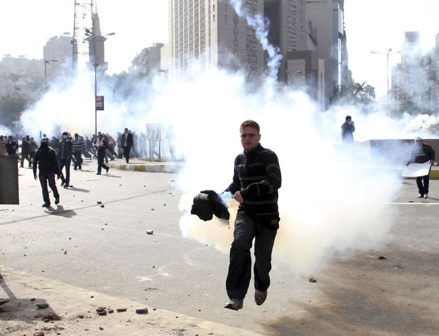 An Egyptian protester flees as anti-riot policemen fire tear gas in Cairo Friday, Jan. 28, 2011. The Egyptian capital Cairo was the scene of violent chaos Friday, when tens of thousands of anti-government protesters stoned and confronted police, who fired back with rubber bullets, tear gas and water cannons. It was a major escalation in what was already the biggest challenge to authoritarian President Hosni Mubarak's 30 year-rule. (AP Photo/Ahmed Ali)