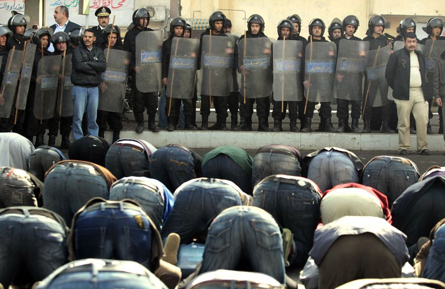 Egyptian riot police officers stand in front of protesters performing Friday prayers in Cairo Friday, Jan. 28, 2011. Tens of thousands of anti-government protesters poured into the streets of Egypt Friday, stoning and confronting police who fired back with rubber bullets and tear gas in the most violent and chaotic scenes yet in the challenge to President Hosni Mubarak's 30-year rule. (AP Photo/Lefteris Pitarakis)