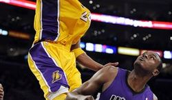 Los Angeles Lakers shooting guard Kobe Bryant, left, dunks over Sacramento Kings center Samuel Dalembert during the second half of their NBA basketball game, Friday, Jan. 28, 2011, in Los Angeles. The Kings won 100-95.  (AP Photo/Mark J. Terrill)
