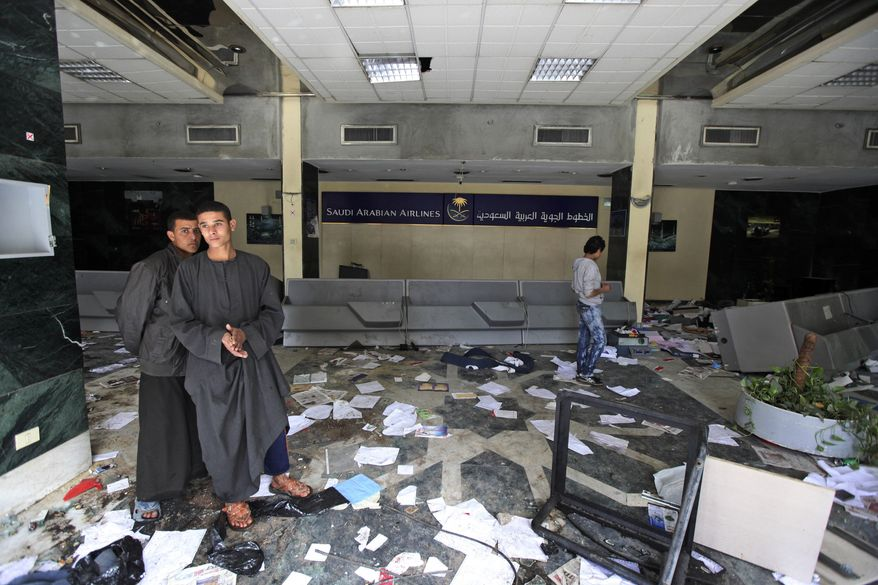 People walk inside the damaged offices of Saudi Arabian Airlines, after they were looted and partially burned by anti-government protesters in Cairo, Egypt, on Saturday, Jan. 29, 2011. (AP Photo/Victoria Hazou)