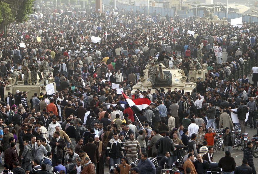 Thousands of Egyptians surround army tanks in downtown Cairo, Egypt, on Saturday, Jan. 29, 2011. Hundreds of anti-government protesters have returned to Cairo's central Tahrir Square, chanting slogans against Hosni Mubarak . (AP Photo/Ahmed Ali)
