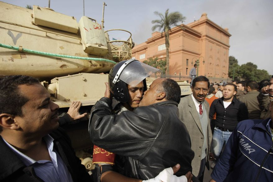 An Egyptian anti-government activist kisses an Egyptian army officer, center back, in Tahrir square in Cairo, Egypt, on Saturday, Jan. 29, 2011. (AP Photo/Ben Curtis)