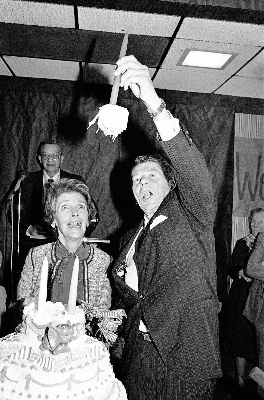 On the presidential campaign trail in Anderson, S.C., on Feb. 6, 1980, Ronald Reagan marks his 69th birthday, pulling up a chunk of the cake along with the candle, as wife Nancy looks on. Festivities will mark his birth centennial this week. (Associated Press)